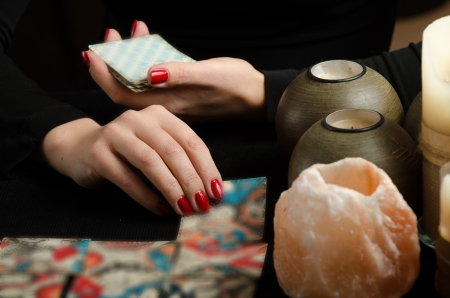 Hands of young woman with divination cards  Stock Photo