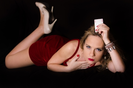 croupier: Woman in red with playing card Stock Photo