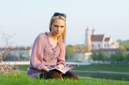 First warm days of the spring in Vilnius, Lithuania  Young sexy woman reading in the evening Stock Photo