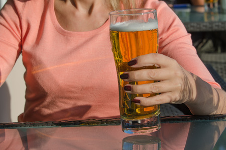 wallop: Hand of woman holding a glass of beer Stock Photo