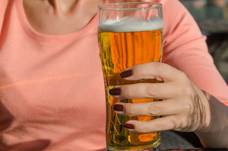 brewage: Hand of woman holding a glass of beer Stock Photo