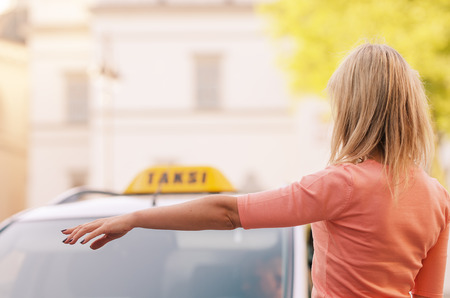 woman raising her arm to call a taxi photo