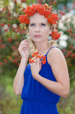 Young woman with rowan (sorbus, mountain ash) crown photo