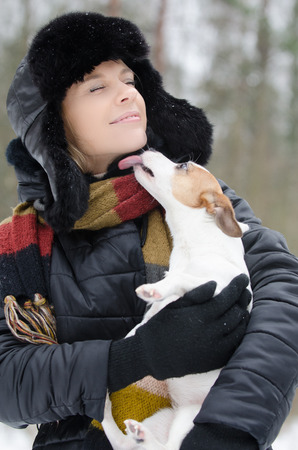 animal eye: Young woman holding Jack Russell terrier in winter time Stock Photo