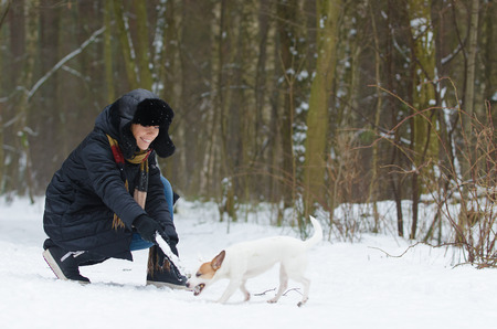 Young woman playing with Jack Russell terrier in winter time Stock Photo