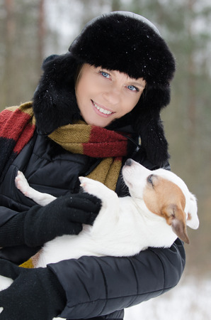 Young woman holding Jack Russell terrier in winter time Stock Photo