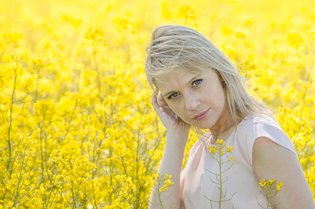 adult rape: Young woman in the rape, colza field Stock Photo