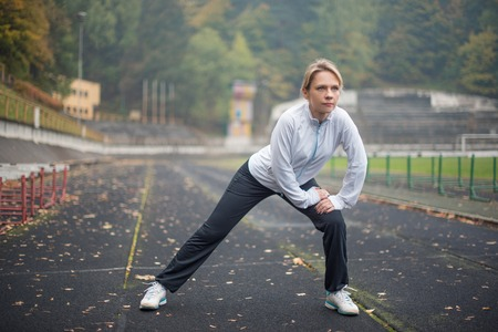 Woman exercising in the stadium, small depth of field Stock Photo