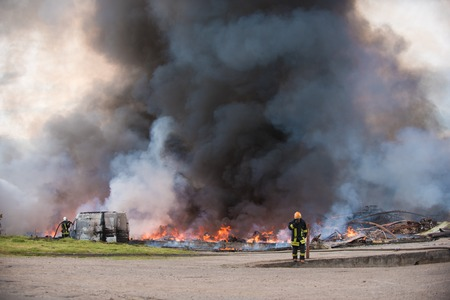 bombera: Un gran incendio de edificios y coches Foto de archivo