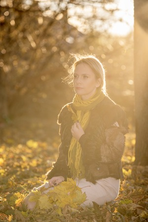 sear and yellow leaf: Woman with autumn leaves in the sunset. Beautiful symbol of autumn