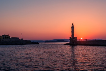 Chania, Crete, Greece: lighthouse in Venetian harbor in the sunset Stock Photo