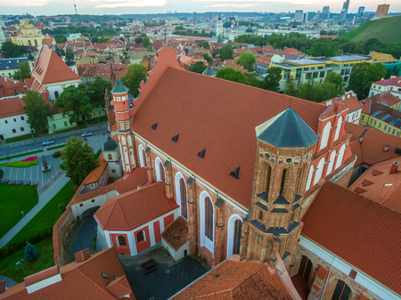 ir: AERIAL. Old Town in Vilnius, Lithuania: St Annes and Bernadines Churches, Lithuanian: Sv. Onos ir Bernardinu baznycios. Representative summer picture Stock Photo