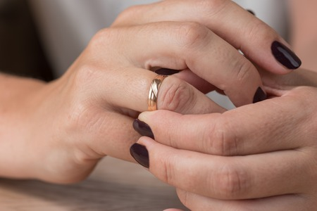 Divorce, separation: hands of woman removing wedding or engagement ring Stock Photo