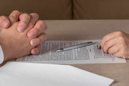 divorcing: Divorce: hands of wife and husband signing divorce documents, woman returning wedding ring