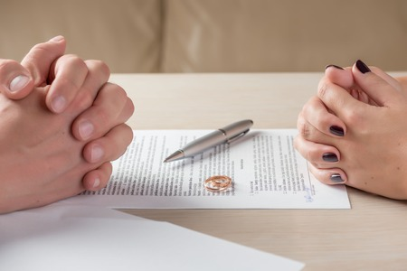 divorcing: hands of wife and husband signing divorce documents or premarital agreement