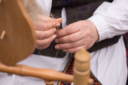 wheel spin: Hands of woman spinning wool into yarn with a spinning wheel