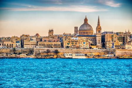Valletta, Malta: skyline van Marsans Harbor bij zonsondergang. De kathedraal