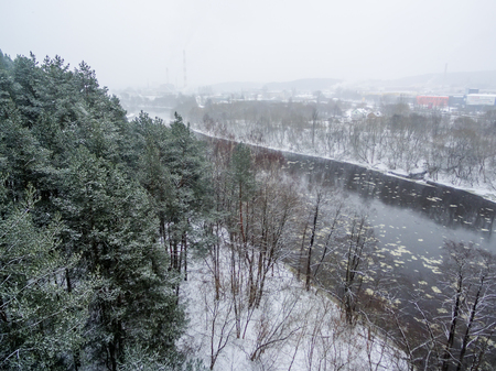 Aerial top view of winter forest and ice drift on the river