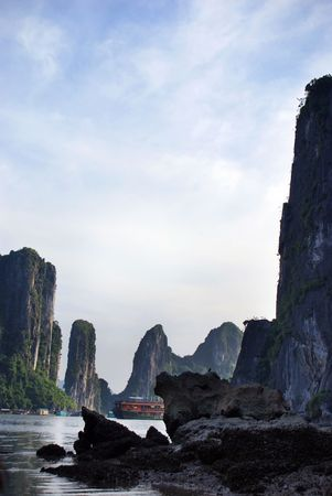 islets: Halong Bay: Protruding rocks with a Junk in the background in Halong Bay.