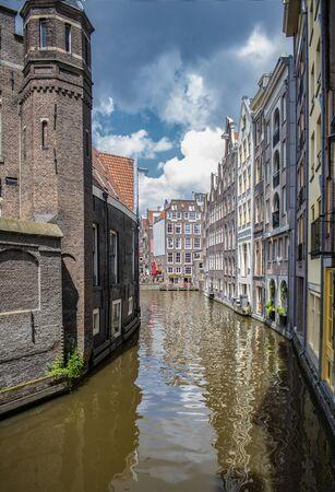 Channel in Amsterdam Netherlands houses river Amstel landmark old european city spring landscape