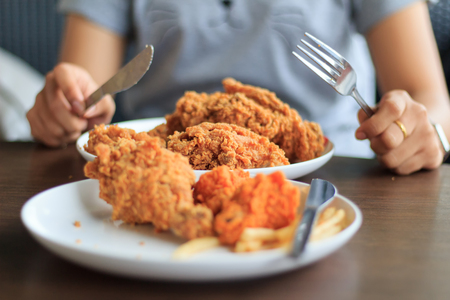 Close-up woman hands holding cutting fried chicken, Eat fried chicken with girlfriend, Select focus fried chicken with blur background, Young woman cutting fried chicken select focus, Fried chicken lunch