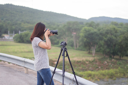 Travel take photo Public landmark, Young women take photo landscape, Woman holding dslr camera for shooting image in holiday,Travel take photo tourist camera photography concept Standard-Bild