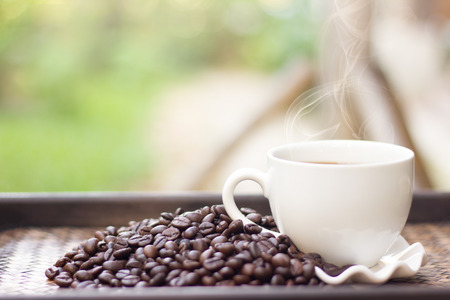 Coffee beans with white coffee mug blur background, A cup of hot coffee is placed beside the coffee beans