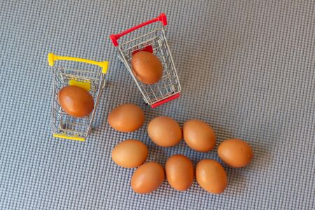 Cart and eggs with yellow background, Concept buying or selling eggs