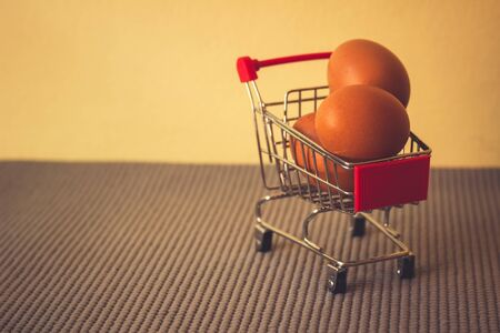 Cart and eggs with yellow background, Concept buying or selling eggs,