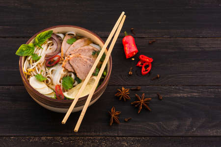 Vietnamese traditional spicy pho bo soup with rice noodles, beef slices, star anise on a dark brown wooden background. Rustic.