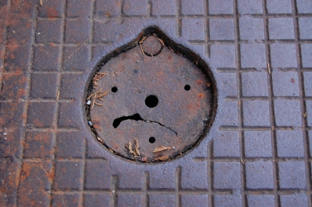 Sad smiley on street iron cover  centred, any photo post proces photo
