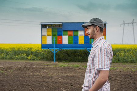truckload: Portrait of young farmer in front of bee house