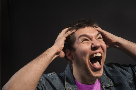 angst: Close-up of a man screaming in agony. Stock Photo