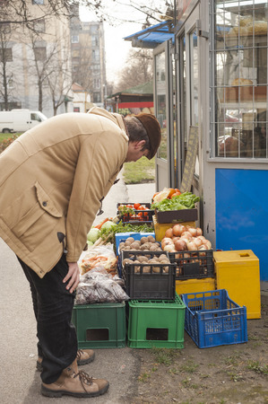 resale: Young man choosing potato  at fruit vegetable market Stock Photo