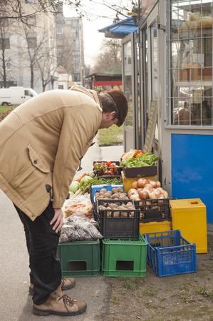 resale: Young man choosing potato  at fruit vegetable market Stock Photo