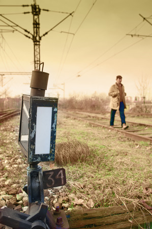 complicated journey: Young man walking on rail road Stock Photo
