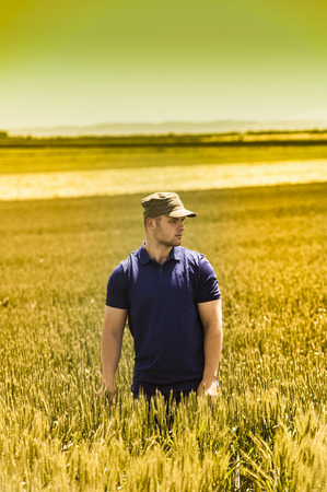 toxicity: Young farmer on field of wheat