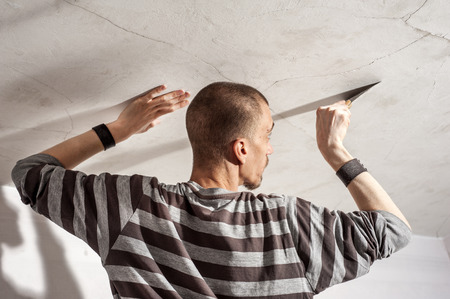 scraping: Worker scraping old paint from wall before new paint Stock Photo