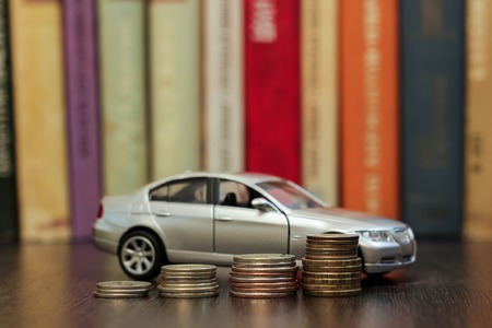 mount price: Car with helping hand on coins and books Stock Photo