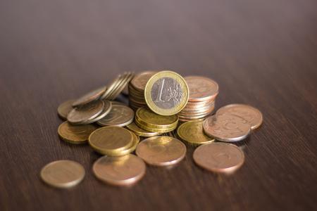 monedas antiguas: pila de monedas rusas sobre un fondo de madera con el euro en el medio