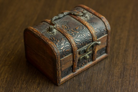 hidden success: closed treasure chest standing on wooden table