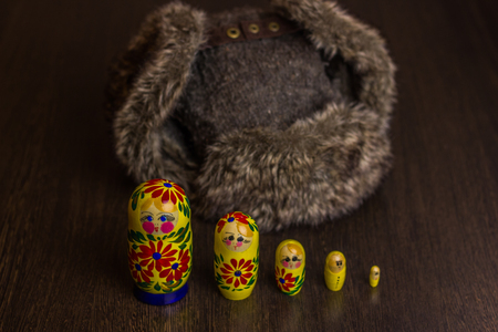 flaps: Winter hat ear flaps with raised ears and matryoshka on wooden table