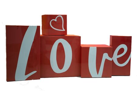 Valentines day greeting card over paper background. Multicolored blocks with letters folded in the word LOVE on empty white card for your text. Top view with copy space,