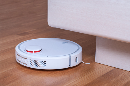 White robot vacuum cleaner runs in bedroom.