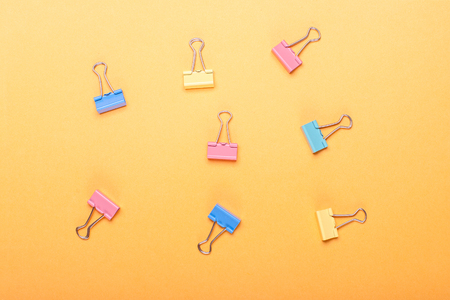 yellow background with colorful paper clip holders.