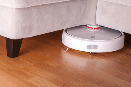 Robotic Vacuum Cleaner Runs Under Sofa In Room On Laminate Floor