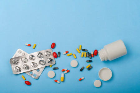 Medicine bottle, blister pack and pills closeup on blue background. Stock Photo