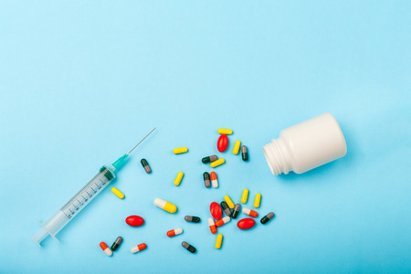 colorful Pills, Medicine bottle and disposable syringe closeup on blue background. Health pharmacy pharmacology concept with Copy Space.