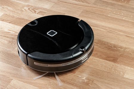 Black robotic vacuum cleaner runs on laminate floor. modern smart cleaning technology housekeeping.