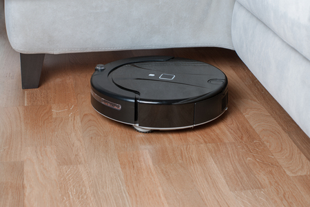 Black robotic vacuum cleaner runs under sofa in room on laminate floor modern smart cleaning technology housekeeping.